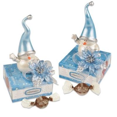 Porzellan-Schneemann auf Box mit feinen Pralinen